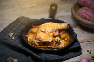Low key of image of Chicken thighs in a cast iron skillet and sweet potato on wooden background