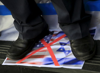 An activist shouts slogans against Israel and the U.S as he stands on a picture of their flags during a protest in front of the Syndicate of Journalists in Cairo