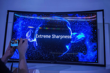 Person takes photo of Curved OLED TV during a news conference in New York