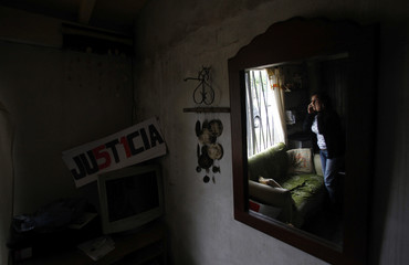 Maria Lujan Rey, mother of Lucas Menghini Rey, the last passenger found dead in the packed commuter train crash at Once train station, is reflected on a mirror as she talks on the phone at her home in San Antonio de Padua