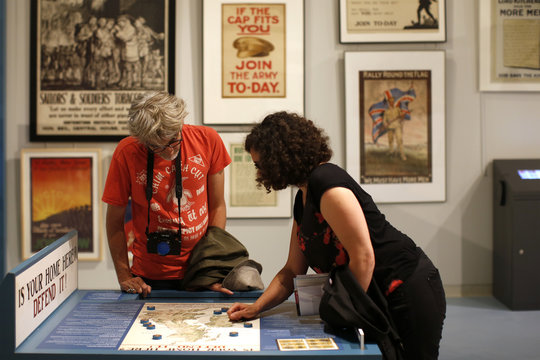 "Visitors look at a map displayed in the exhibition ""Join Now! The British Empire's Entry into The War"" at the Museum of the Great War in Meaux"