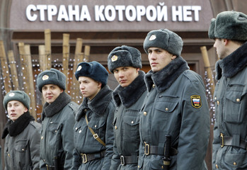 Russian police observe a march by Communist Party supporters to mark the Defender of the Fatherland Day in Moscow