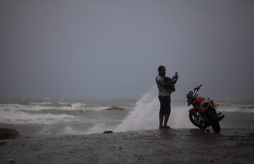 A man takes pictures on an old pier ahead of Hurricane Matthew in Les Cayes, Haiti