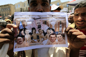 An anti-government protester shows a cartoon depicting Arab leaders as babies during a rally to demand the ouster of Yemen's President Ali Abdullah Saleh, in Sanaa