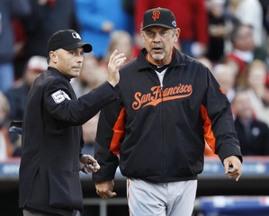 Home plate umpire Lassogna points to the bull pen as San Francisco Giants manager Bochy brings in pitcher Lincecum  during their MLB NLDS playoff against Cincinnati Reds in Cincinnati