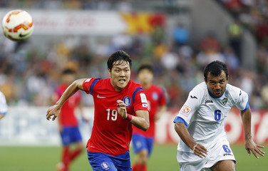 South Korea's Kim Young-gwon and Uzbekistan's Bakhodir Nasimov chase the loose ball during their Asian Cup quarter-final soccer match at the Rectangular stadium in Melbourne