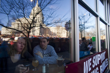 The Wisconsin State Capitol is reflected against a restaurant window together with people gathered to protest against a proposed legislation by Republican Governor Walker in Madison