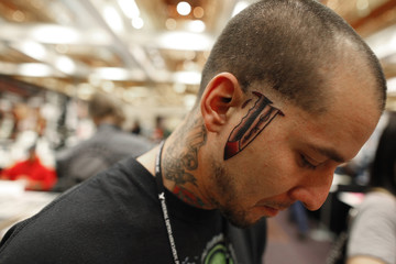 A client shows his new knife tattoo, which appears on both sides of his face, at National Tattoo Association Convention in Cincinnati