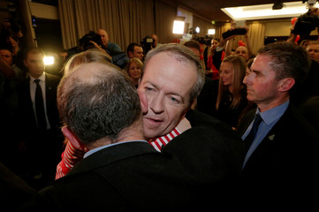 Australian Labor Party opposition leader Bill Shorten hugs a supporter at his election night party in Melbourne