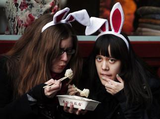 Tourists wearing bunny ears eat dumplings at the Yuyuan Garden in downtown Shanghai