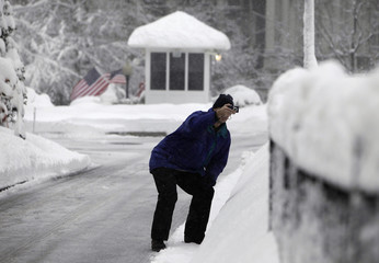A member of the media takes pictures of snow around the White House in Washington