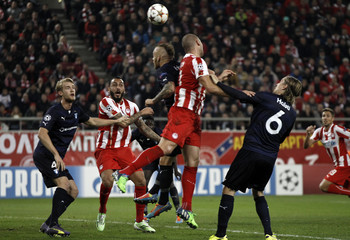 Olympiakos' Kasami jumps for the ball against Malmo's Eriksson during their Champions League soccer match in Piraeus