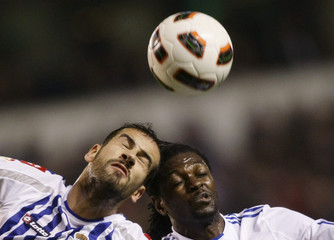 Deportivo La Coruna's Lopo jumps for the ball with Real Madrid's Adebayor during their Spanish First Division soccer match in Coruna