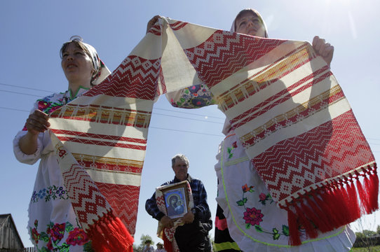 A villager carries an icon of the Mother of God behind women carrying a scarf during a ritual celebrating the pagan god Yurya in Pogost