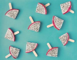 beautiful fresh sliced popsicles dragon fruit like background, Pitaya, flat lay on blue background, instagram style