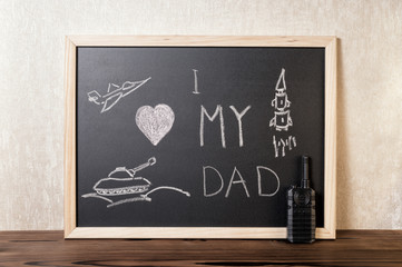concept of Father's Day with handwritten text I love my  Dad, pictured airplane, tank, rocket on blackboard over wooden background and toy