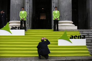 A man takes a photo before the stock market debut of the Spanish airports group Aena outside the bourse in Madrid