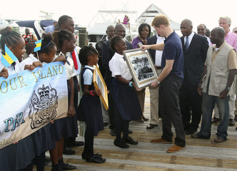 Britain's Prince Harry is presented with a framed photo during a tour of Harbour Island in Nassau