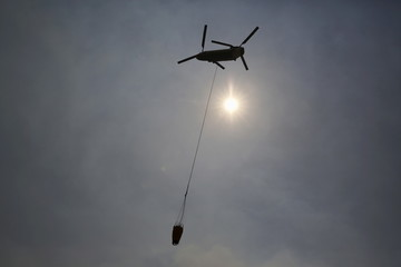 A firefighting helicopter takes a load of water to fight the Wragg Fire near Lake Berryessa