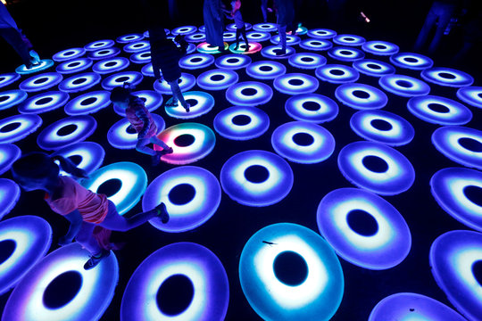 """People interact with """"Luminous Lawn"""" which is part of the exhibit """"Enchanted: Forest of Light"""" at Descanso Gardens in La Canada Flintridge"""