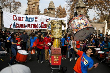 Protesters play drums next to a mock Copa America soccer tournament cup during a demonstration to demand changes in the education system, in Santiago