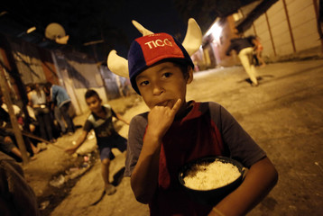 A boy eats food in Triangulo de la Solidaridad, a low-income neighbourhood, north of San Jose