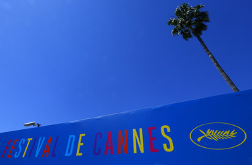 A security camera and a palm tree are seen above a poster of the 67th Cannes Film Festival near the Port of Cannes on the eve of the opening of the Festival in Cannes