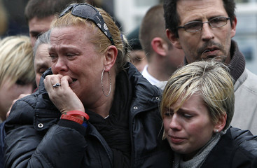 Mourners weep as the hearses carrying the coffins of three British soldiers are driven through the streets of Wootton Bassett