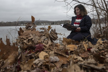 Recent refugee from Syria Sandy Khabbazeh reads by a lake, her favorite place to relax in Oakland, New Jersey