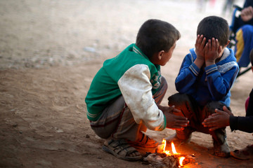 Displaced Iraqi boys, who fled the Islamic State stronghold of Mosul, warm themselves by a fire at Khazer camp