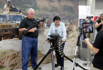Gun enthusiasts poses for a picture with an FN MK 48 machine gun and a MK 19 grenade launcher at the National Rifle Association's annual meetings & exhibits show in Louisville
