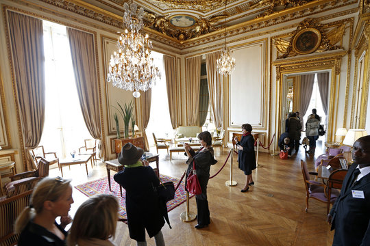 Visitors take pictures of furniture displayed for auction at the Hotel de Crillon in Paris