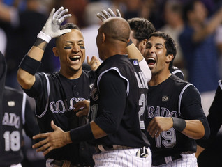 Colorado Rockies players Carlos Gonzalez, Miguel Olivo and Ryan Spilborghs celebrate defeating the Boston Red Sox in Denver