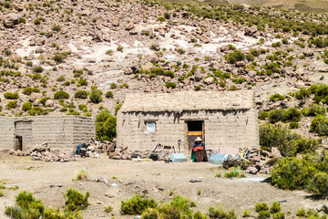 SOUTHWESTERN BOLIVIA - APRIL 16, 2015: Indiegenous woman sits at the adobe house in a small settlement,