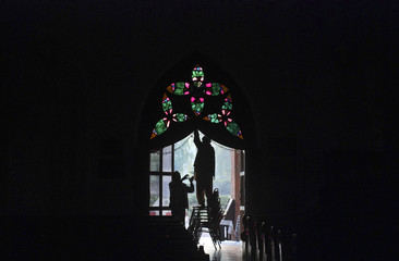 Men are silhouetted as they decorate a door at the St Johns Cathedral Church, on Christmas eve in Peshawar