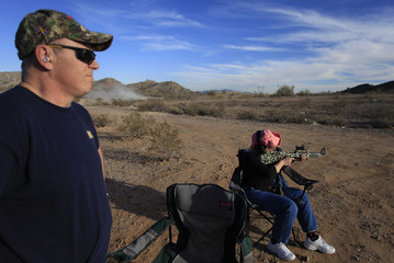 National Rifle Association instructor and retired Navy Warrant Officer Scheutzow watches as his wife shoots her .22 caliber gun along a mountain range in Buckeye
