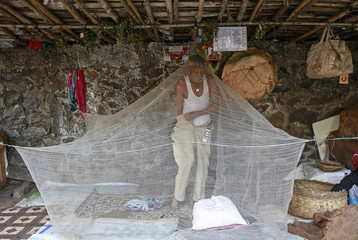 A vendor gets dressed under a mosquito net at his roadside shop in Mumbai
