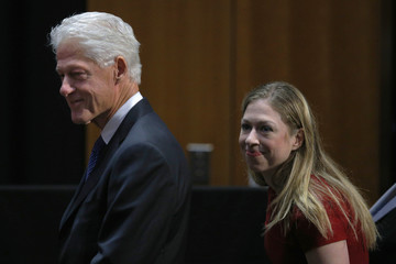Former United States President Clinton and his daughter Chelsea take their seats before being honored at a ceremony at Harvard University's School of Public Health in Boston