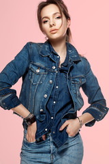 Portrait of a fashionable young woman in a denim jacket, jeans and a denim shirt on a pink background