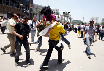 A protester carries another protester injured by tear gas on a street around Tahrir Square in Cairo