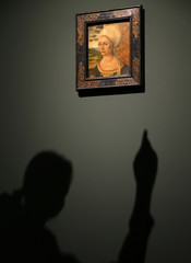 Woman casts her shadow as she points towards painting 'Portrait of Elsbeth Tucher' by Duerer during pre-view of Duerer exhibition at Staedel museum in Frankfurt