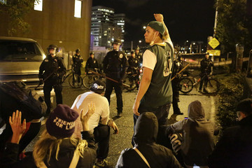 Police officers block a freeway as protesters march the day after the grand jury decision in the shooting of Brown, in Seattle