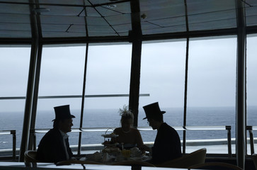 Passengers enjoy traditional afternoon tea as they sit in a top floor lounge on board the Titanic Memorial Cruise in the mid-Atlantic Ocean