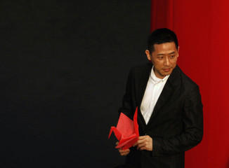 Tong, partner of late Hong Kong singer and actor Cheung, holds an origami crane in Hong Kong