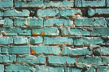 A piece of old painted in green brick wall paint, a brick texture. Abstract background.