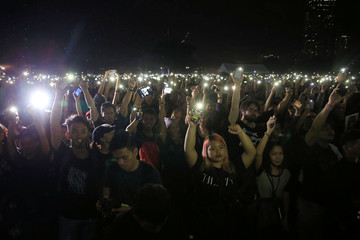 Protesters raise their mobile phones during a protest denouncing the burial of late dictator Ferdinand Marcos inside Heroes' cemetery last week, at Luneta park, metro Manila