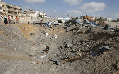A Palestinian inspects a crater which police said was caused by an Israeli air strike in Gaza City