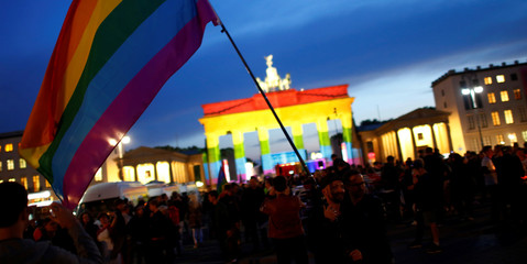 People stand in front of Brandenburg gate, lit up in support of the victims killed in an Orlando gay nightclub, in Berlin