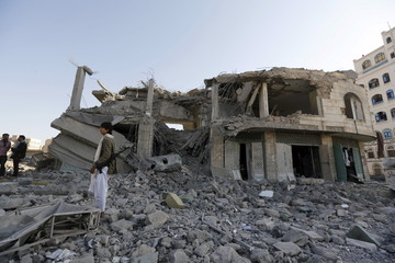 A Houthi militant stands guard outside the house of court judge Yahya Rubaid after a Saudi-led air strike destroyed it, killing him, his wife and five other family members, in Yemen's capital Sanaa