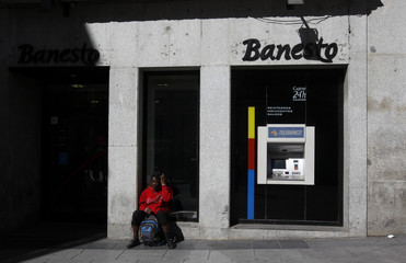 A woman sits at a Banesto bank branch in central Madrid